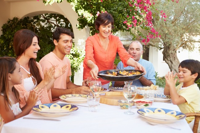student with host family with student having paella